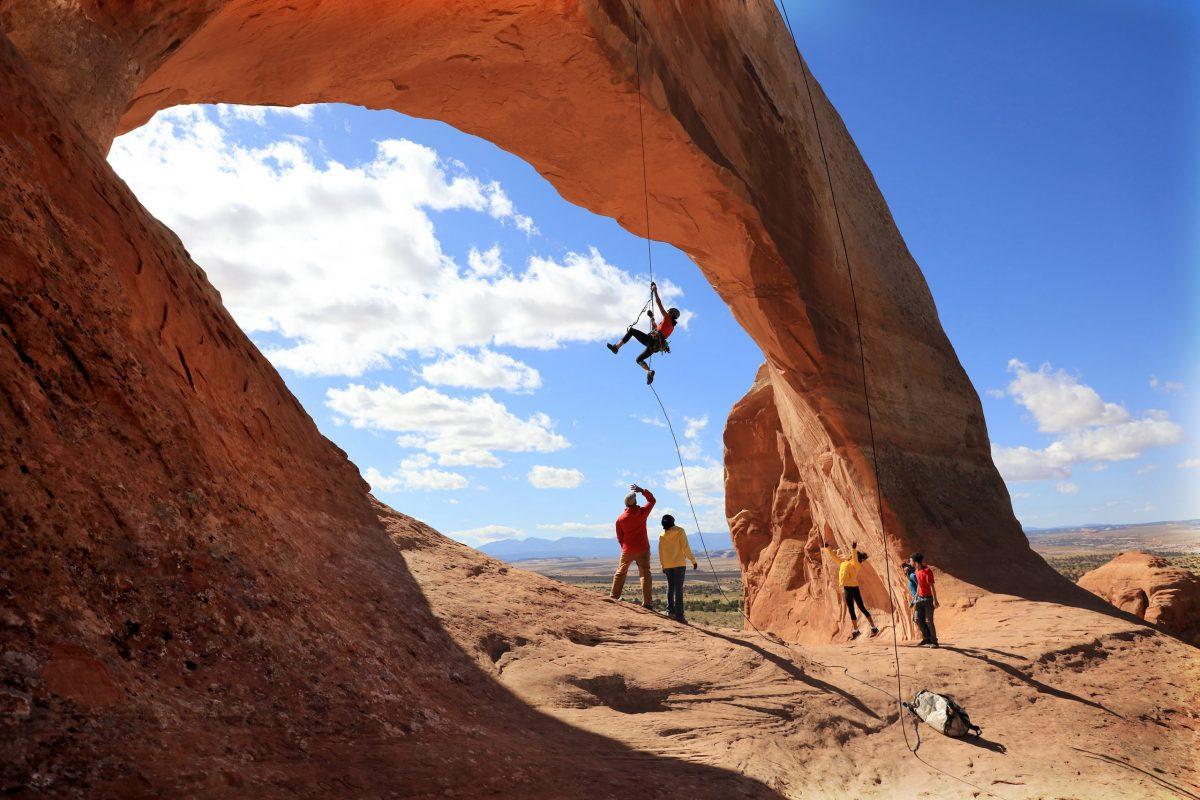 Climber Miranda Oakley dangles delicately under Wilson's Arch in Moab, Utah.