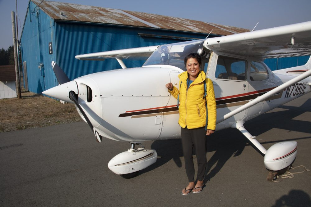 Alaskan Native, Ariel Tweto, stands in front of the Cessna 172 that she piloted along the southern Oregon Coast