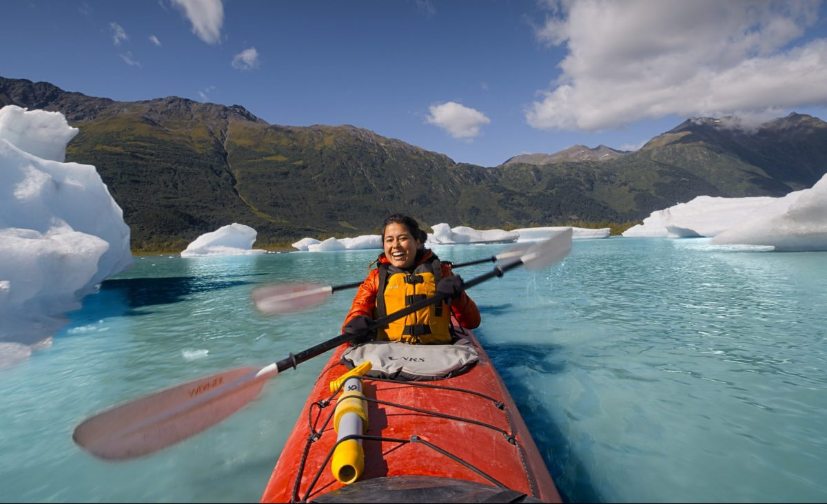 Ariel Tweto paddles a tandem kayak through the arctic blue waters of Spencer Glacier in Chugach National Forest, Alaska.