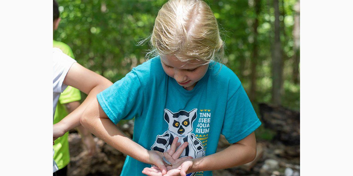 summer camper holding bug